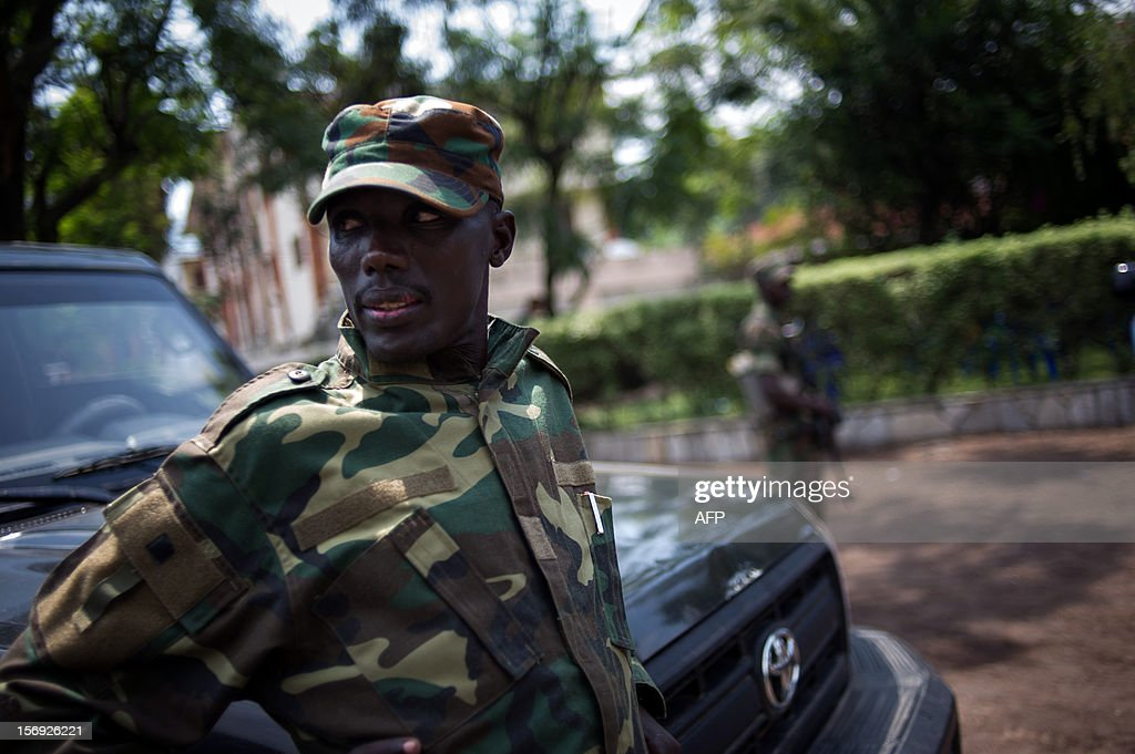 The head of the M23 rebel military forces, Brigadier-General Sultani Makenga (R), leans on a car on November 25, 2012 on the grounds of a military residence in Goma in the east of the Democratic Re...