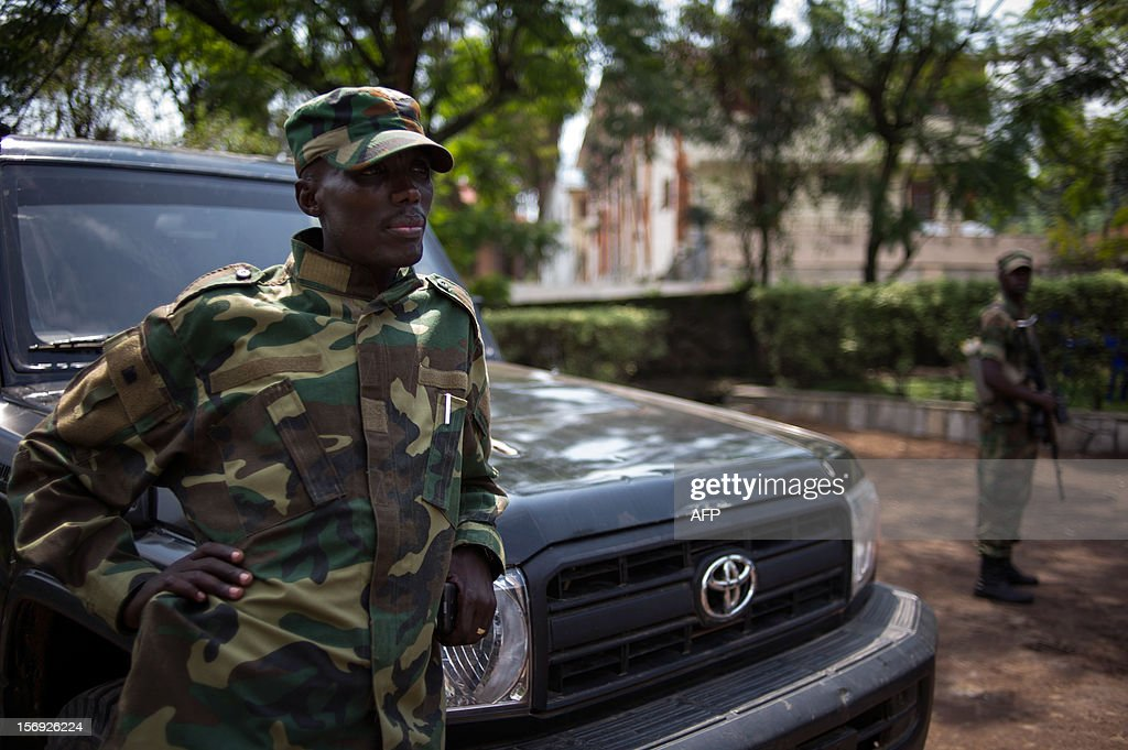 The head of the M23 rebel military forces, Brigadier-General Sultani Makenga (R), leans on a car on November 25, 2012 on the grounds of a military residence in Goma in the east of the Democratic Republic of the Congo. Over half a million people have been displaced in eastern Congo since the outbreak of the M23 rebellion. Diplomatic efforts continued on November 25 to resolve the crisis in eastern DR Congo, with an M23 rebel leader expected to hold further talks with President Joseph Kabila as the African Union called on the rebels to pull out from Goma.