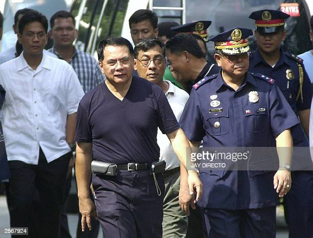 The head of the Philippine national police, Director General Hermogenes Ebdane exits the police compound where three policemen and an Abu Sayyaf...
