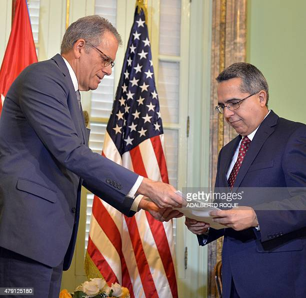 The head of US Interest Section Jeffrey DeLaurentis gives Cuban Foreign ViceMinister Marcelino Medina a letter from US President Barack Obama to...