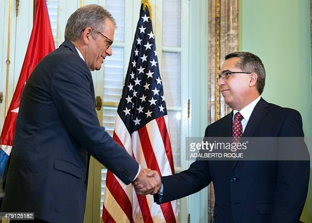 The head of US Interest Section Jeffrey DeLaurentis shakes hands with Cuban Foreign ViceMinister Marcelino Medina after giving him a letter from US...