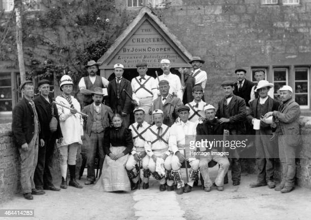 The Headington Quarry Morris Dancers posing with locals outside the public house entrance to the Chequers Oxford Oxfordshire c1860c1922