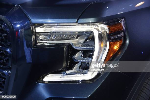The headlight of a General Motors Co 2019 GMC Sierra Denali truck is seen during an event at Russell Industrial Complex in Detroit Michigan US on...