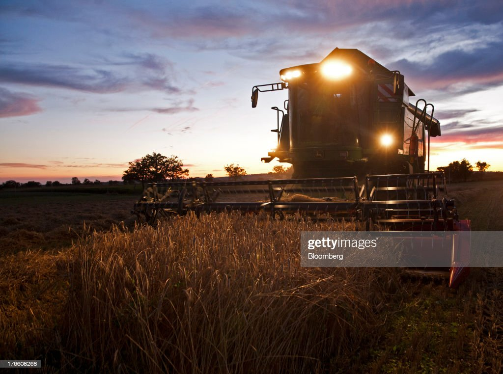 The headlights of a Deere & Co. John Deere W540 combine harvester illuminate a field of triticale wheat during an evening harvest in Falguieres, southwest France, on Thursday, Aug. 15, 2013. French farmers harvested better-quality wheat than expected north and east of Paris, making up for low protein content in the southwest and raising confidence the grain will meet export requirements. Photographer: Balint Porneczi/Bloomberg via Getty Images