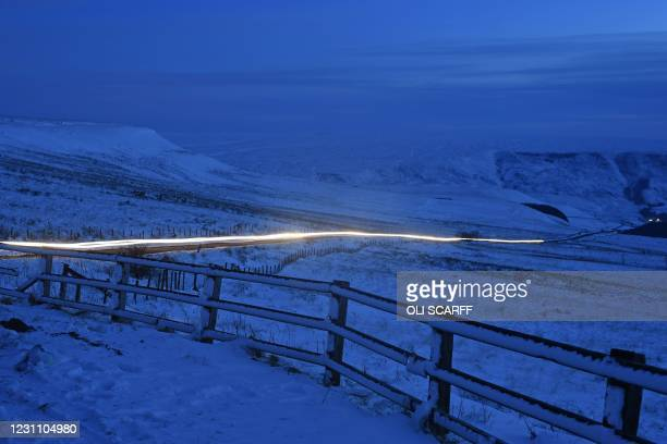 The headlights of traffic are seen between snow-covered fields, on Woodhead Road from Holme Moss in The Peak District in northern England on February...