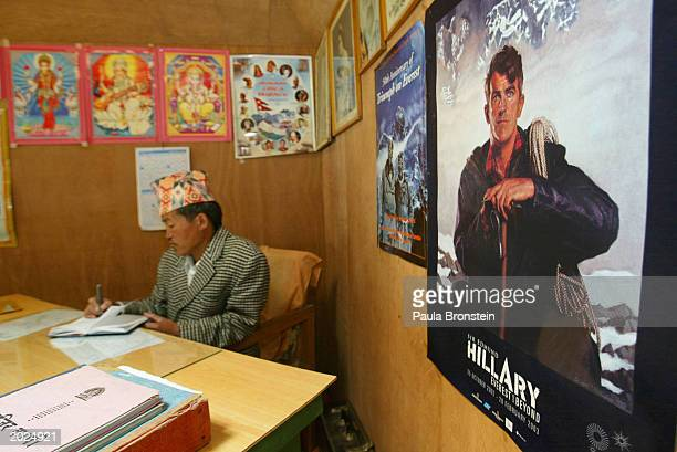 The headmaster of the Mahendra Jhoti Secondary school works in his office along side posters of Sir Edmund Hillary May 23 2003 in the Himalayan Solu...