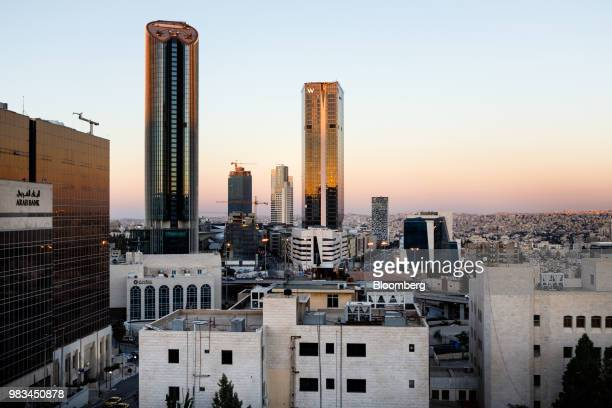 The headquarters of Arab Bank Plc left and Al Abdali district sits on the city skyline as the sun sets in Amman Jordan on Thursday June 21 2018...