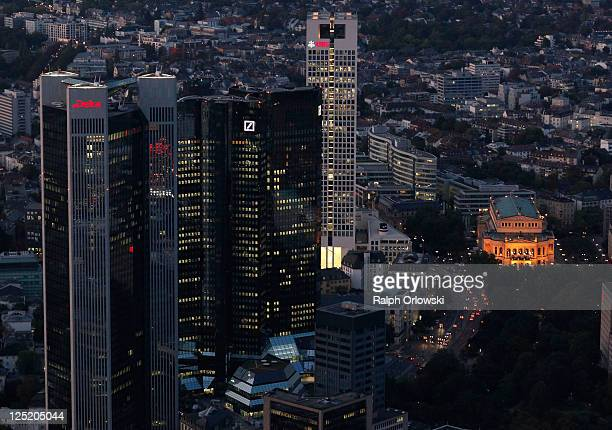 The headquarters of DekaBank the twin towers of Deutsche Bank and UBS Germany stand illuminated in this aerial picture of the financial district on...