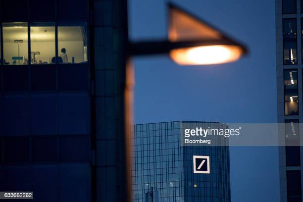 The headquarters of Deutsche Bank AG stand beyond illuminated office space at night in Frankfurt Germany on Thursday Feb 2 2017 Frankfurt expects as...