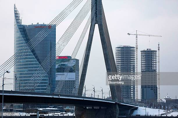 The headquarters of Swedbank AB left stands near an OAO Lukoil advertisement and tower blocks under construction beyond the Vansu bridge in Riga...