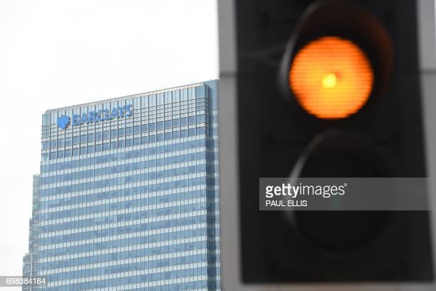 The headquarters of the British bank Barclays is seen at the Canary Wharf district of east London on June 20, 2017 with a traffic light in the...