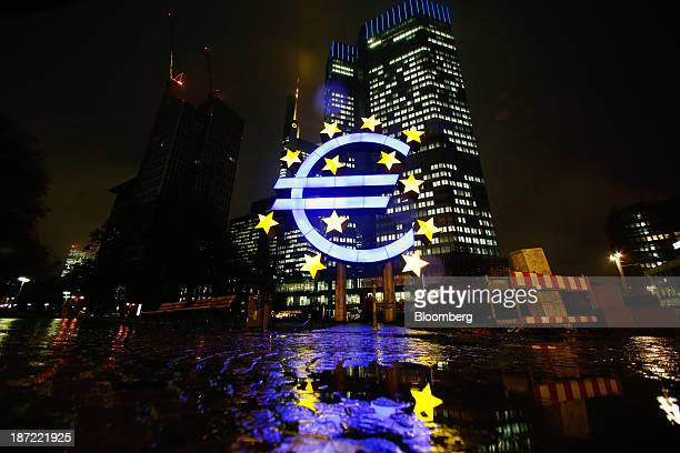 The headquarters of the European Central Bank stands illuminated beyond a euro sign sculpture at night in Frankfurt Germany on Wednesday Nov 6 2013...