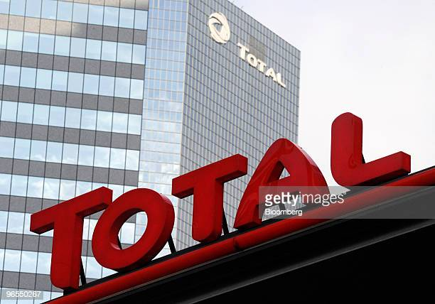 The headquarters of Total SA stand behind a gas station on the Esplanade de la Defense in Paris France on Wednesday Feb 10 2010 The company releases...