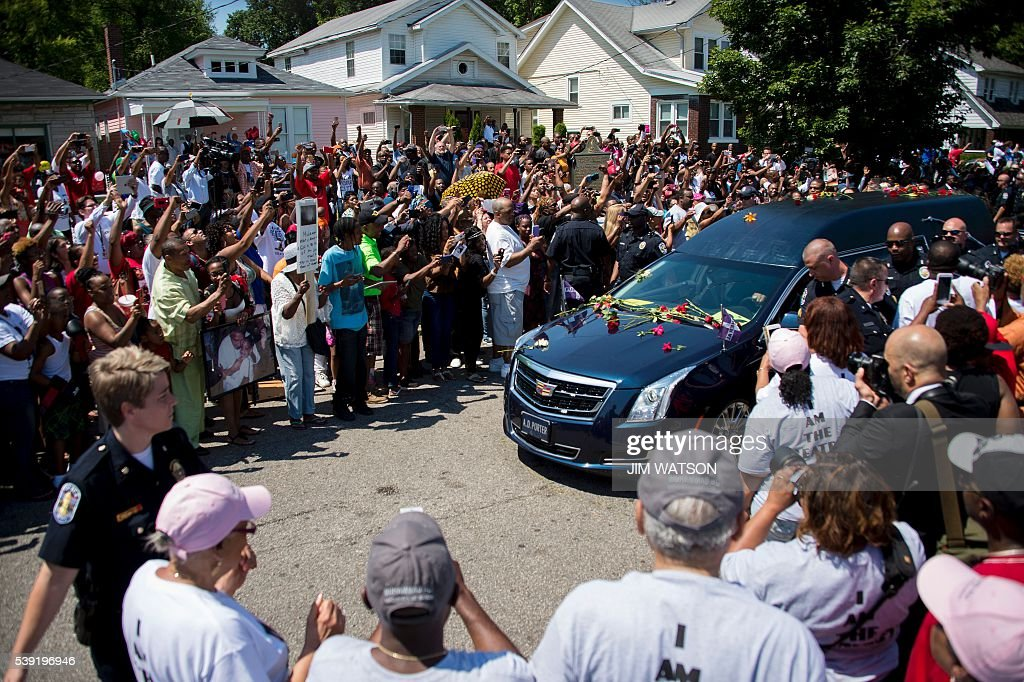TOPSHOT - The hearse carrying boxing legend Muhammad Ali stops outside his childhood home where mourners wait to pay their respects on June 10, 2016 in Louisville, Kentucky. Thousands of people from near and far were expected to line the streets of Muhammad Ali's hometown Louisville on Friday to say goodbye to the boxing legend and civil rights hero, who mesmerized the world with his dazzling skills. / AFP / JIM