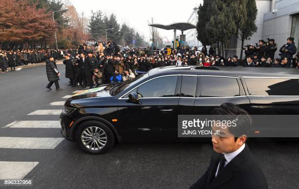 The hearse carrying the body of late SHINee singer Kim JongHyun leaves as fans watch at a hospital in Seoul on December 21 2017 Kim a 27yearold lead...
