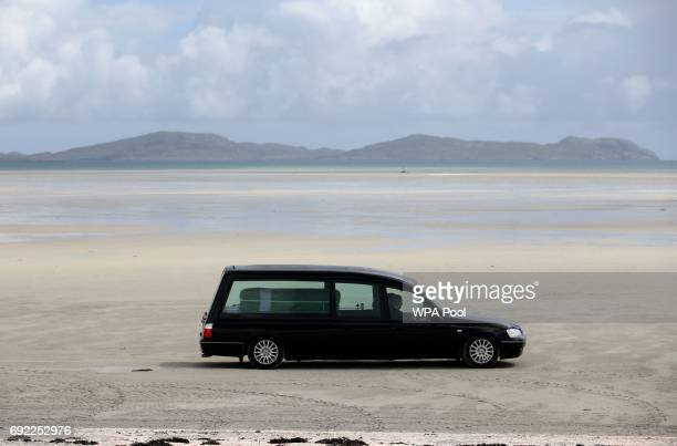 The hearse carrying the coffin of Eilidh MacLeod draped in the Barra flag is driven across Traigh Mhor beach at Barra airport after it arrived by...