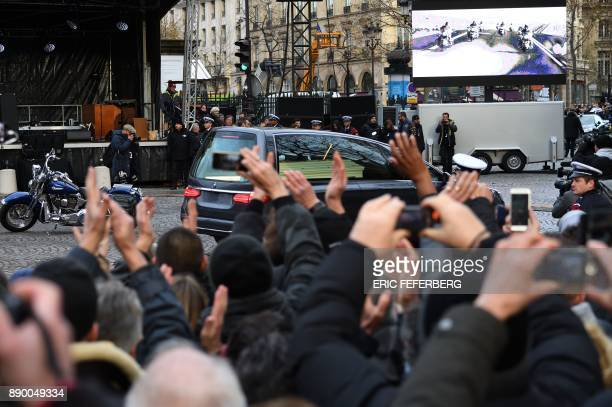The hearse transporting the coffin of late French musician Johnny Hallyday drives past Hallyday's Harley Davidson motorbike as it leaves the La...