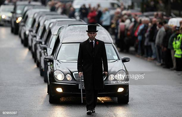 The hearses carrying the coffins of six dead soldiers pass mourners lining the High Street on November 10 2009 in Wootton Bassett England Warrant...