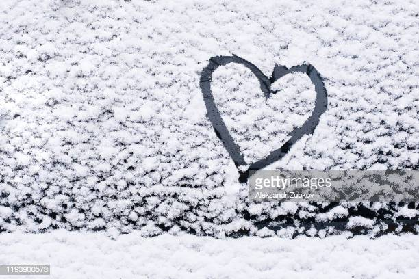 the heart is painted on the glass of the car, on the background of snow. symbol of love, romance, valentine's day. - february stock pictures, royalty-free photos & images