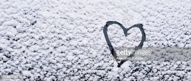 the heart is painted on the glass of the car, on the background of snow. symbol of love, romance, valentine's day. - february background stock pictures, royalty-free photos & images