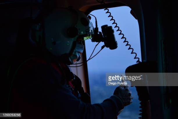 The Helicopter emergency medical staff looks out of the window during a night operation on June 26, 2020 in Turin, Italy. The HEMS helicopter rescue...