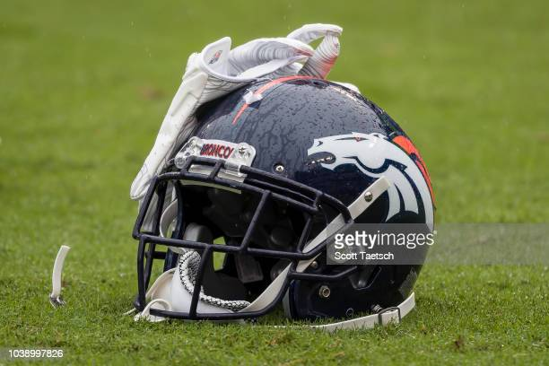 The helmet and gloves of Will Parks of the Denver Broncos rests on the field before the game between the Baltimore Ravens and the Denver Broncos at...