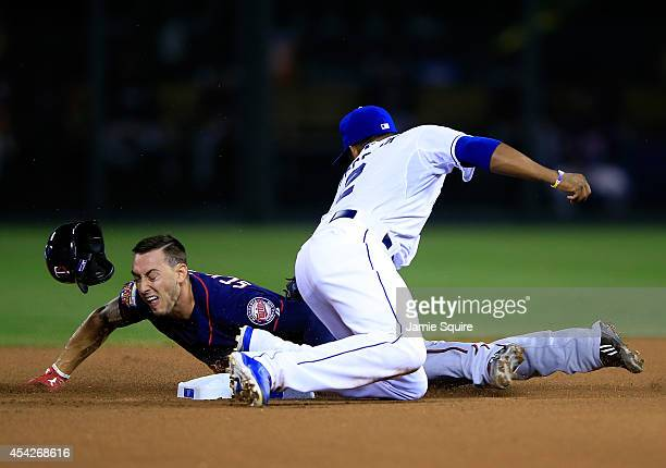The helmet of Jordan Schafer of the Minnesota Twins pops off as he slides safely into second base for a steal as Alcides Escobar of the Kansas City...