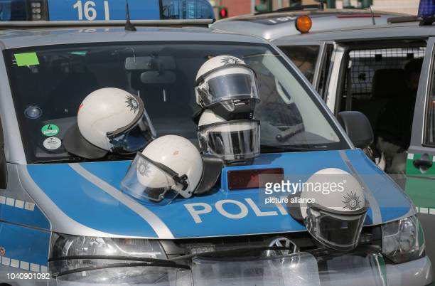 The helmets of police officers having a break lie on a police car after demonstrations near the new headquarters of the European Central Bank opened...