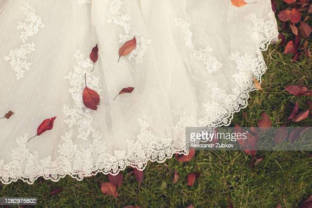 the hem of a white wedding openwork silk expensive luxury bride's dress, against the background of yellow autumn fallen leaves. copy of the space. - 裾 ストックフォトと画像