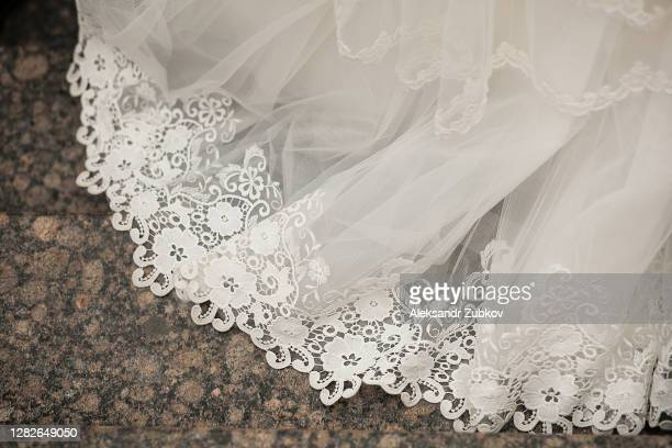 the hem of the white wedding openwork silk expensive luxury bride's dress. copy of the space. - 裾 ストックフォトと画像