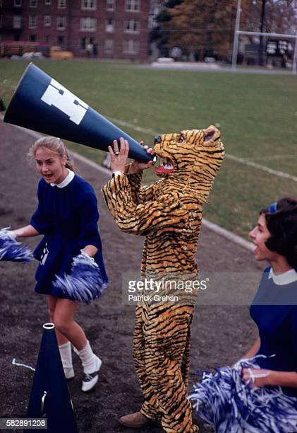 The Hempstead High School tiger mascot cheers with the cheerleaders during a 1960 football game against Freeport High on Long Island