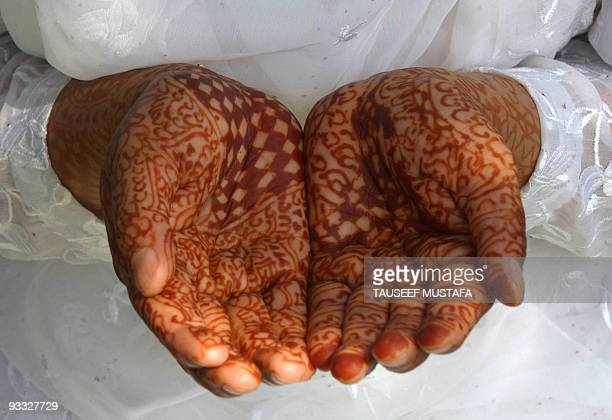 The hennaed hands of a Kashmiri Muslim are held in prayer as an unseen custodian holds a Holy Relic believed to be a hair from the Prophet Mohammed's...