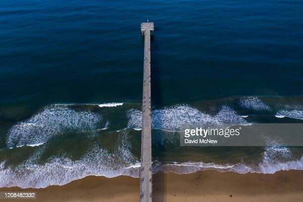 The Hermosa Beach Pier stand deserted as authorities enforce a hard closure of the beaches to stop people from gathering too closely during the...
