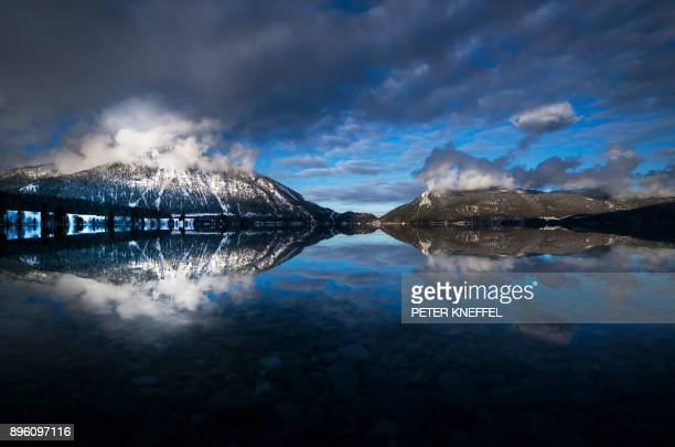 The Herzogstand mountain spotlighted by the afternoon sun reflects in the water of the Walchensee lake near Einsiedel southern Germany on December 20...