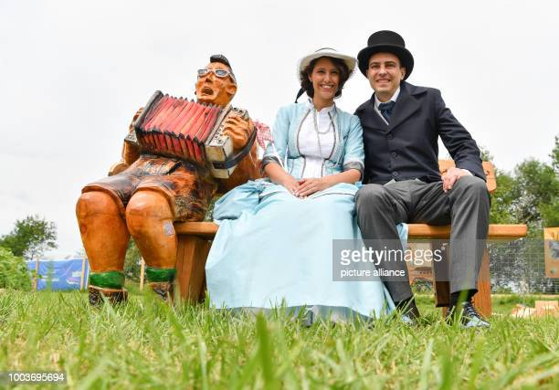 The Hessian Day couple Selma Kücükyavuz and Marcel Sedlmayer sit on a bench next to a wooden figure on the grounds of the exhibition 'Natur auf der...