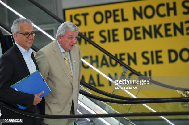 The Hessian Premier Volker Bouffier and his deputy the Hessian Minister of economy Tarek AlWazir walk past a banner saying 'Ist Opel noch wie sie...