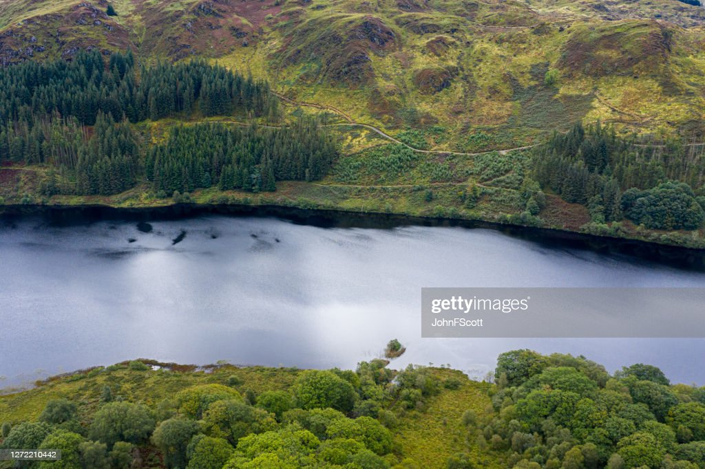 The high angle view from a drone of a calm Scottish loch in rural Dumfries and Galloway : Stock Photo