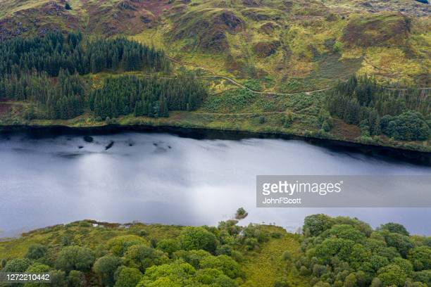 the high angle view from a drone of a calm scottish loch in rural dumfries and galloway - johnfscott stock pictures, royalty-free photos & images