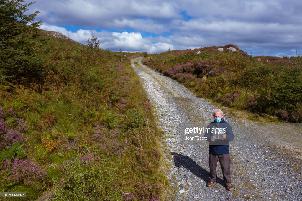 The high angle view of an active senior man wearing a face mask while standing on a dirt road in a remote part of Dumfries and Galloway, south west Scotland : Stock Photo