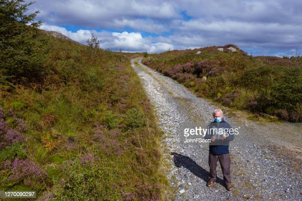 the high angle view of an active senior man wearing a face mask while standing on a dirt road in a remote part of dumfries and galloway, south west scotland - johnfscott stock pictures, royalty-free photos & images