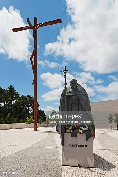 the high cross and a statue of pope john paul ii at the basilica of fatima