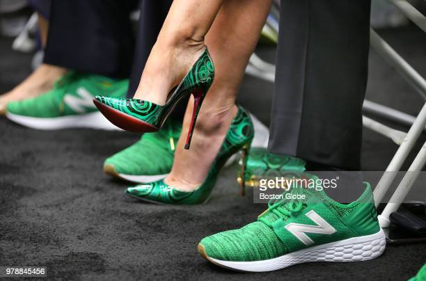 The high heels worn by Emilia Fazzalari wife of Boston Celtics CEO Wyc Grousbeck are pictured next to Grousbeck's green New Balance basketball shoe...