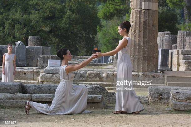 The High Priestess Thalia Prokopiou hands over the flame during the Olympic flame ceremony at the Temple of Hera for the Salt Lake City Winter Games...