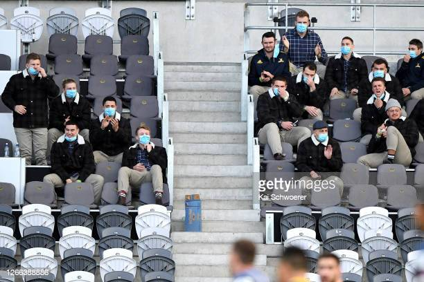 The Highlanders reserve players wear face masks in the empty stands during the round 10 Super Rugby Aotearoa match between the Highlanders and the...