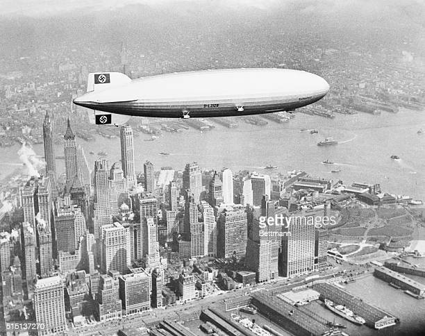 The Hindenburg flies over lower Manhattan on her maiden transatlantic flight Past the tail of the zeppelin can be seen the Bank of Manhattan Building...