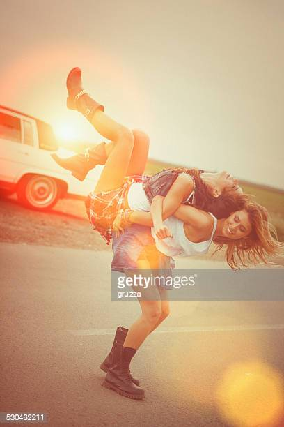 The hipster girl rides piggyback on her female friend