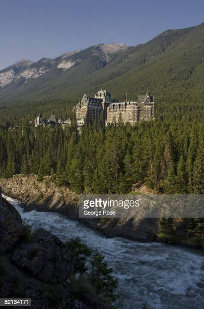 The historic Fairmont Banff Springs Hotel rises above the forest and the Bow River in this 2008 Banff Springs Canada summer sunrise landscape photo