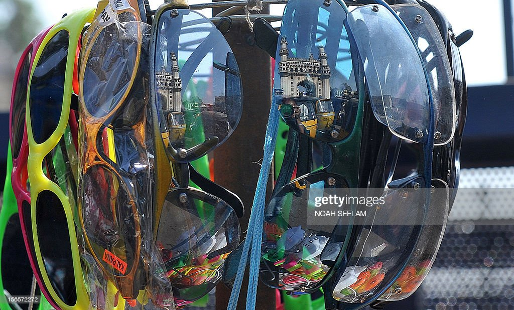 The historic monument Charminar is reflected in spectacles hanging up for sale in the old city of Hyderabad on November 17, 2012. Restrictions were lifted on the movement of people and vehicular traffic around Charminar, where a mob indulged in stone pelting and trouble broke out after the noon prayers following the controversy over the newly erected structure near the Bhagyalaxmi temple. Muslims, supported by the Majlis-e-Ittehadul Muslimeen (MIM) party, opposed the move fearing that the temporary structure would pave the way for the permanent construction of a larger temple near the Charminar monument. AFP PHOTO / Noah SEELAM