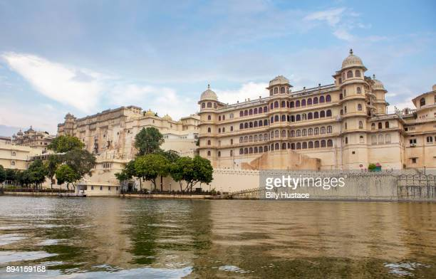 The historical City Palace in Udaipur, India features Rajput-style architecture overlooking famous Lake Pichola