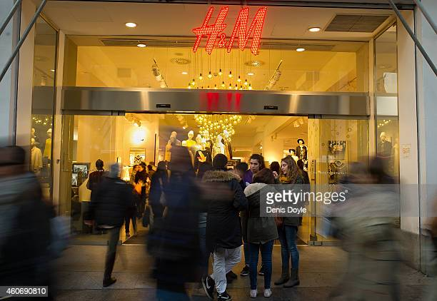 The HM logo is seen in the window display of a Hennes Mauritz AB clothing fashion on Gran via street on December 19 2014 in Madrid Spain Shoppers...